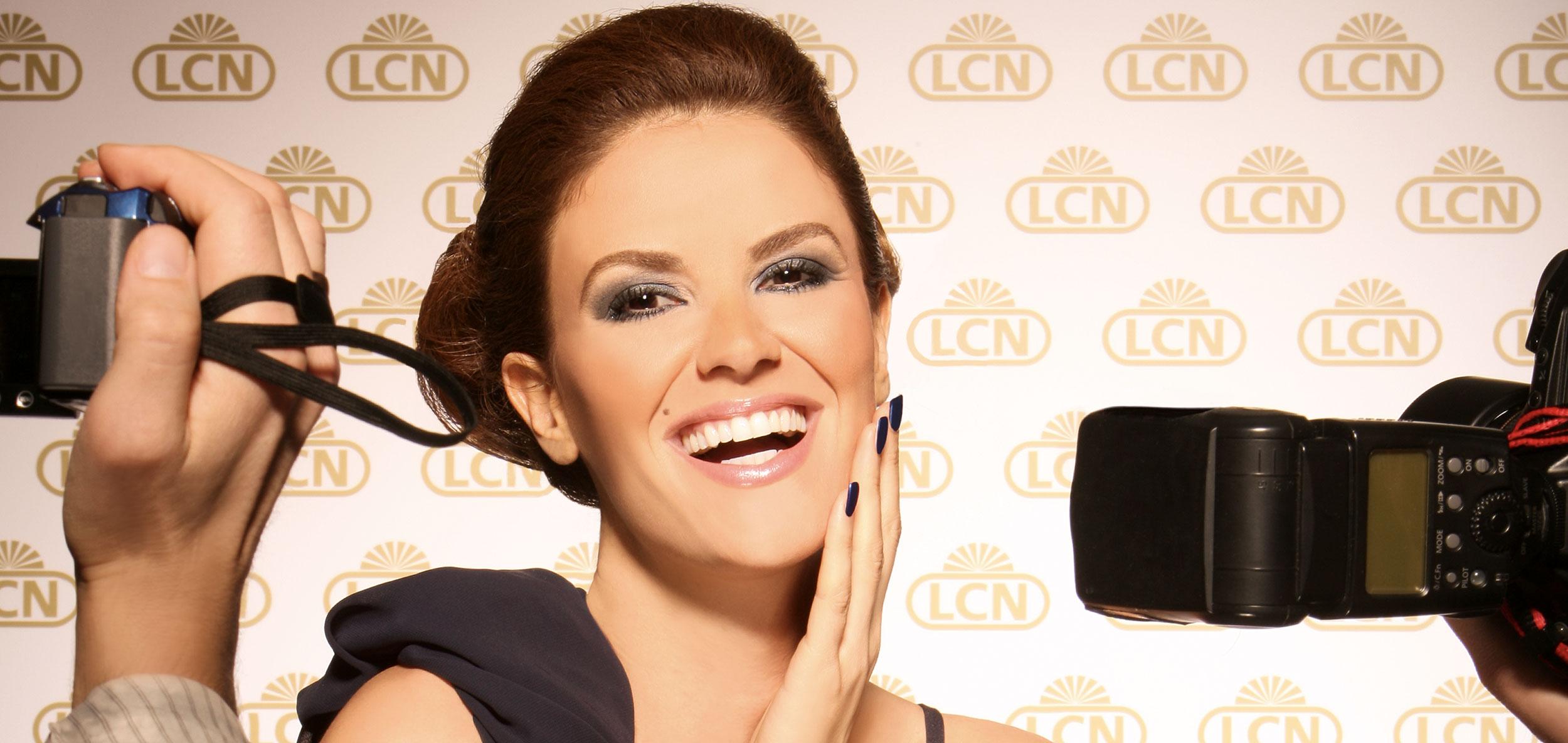 Modell som fotograferes forran en vegg med LCN-logo