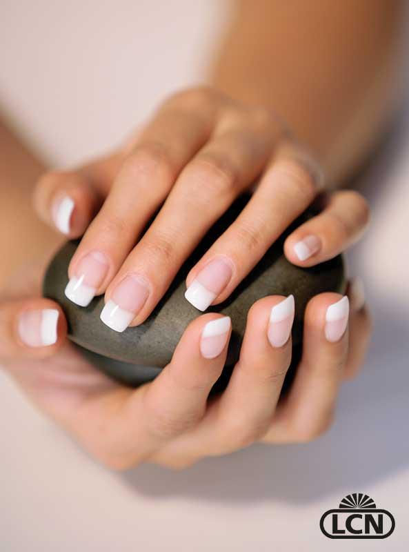 Vakre hender med franske gelénegler, som holder en stein